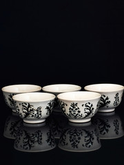 white Japanese tea cups on black