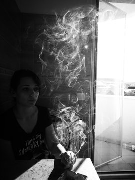 Young Woman Smoking Cigarette In Restaurant