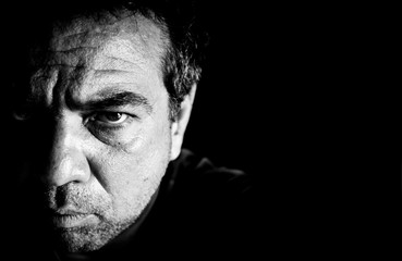 Portrait Of Angry Man Against Black Background