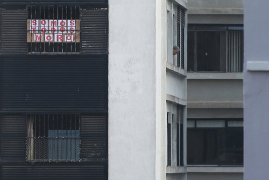 """A man looks out of his window next to a banner that reads: """"we are all Moro"""" during a protest against a speech given by Brazil's President Jair Bolsonaro after Justice Minister Sergio Moro announced his resignation, in Sao Paulo"""