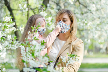 Mother and daughter with a masks on faces are in the city outdoor, blooming trees, spring season, flowering time - concept of allergies and health protection from dusty air