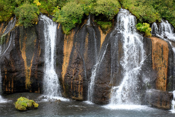 Hraunfossar / Iceland - August 15, 2017: Hraunfossar waterfalls formed by rivulets streaming out of the Hallmundarhraun lava field formed by the eruption of a volcano, Iceland, Europe