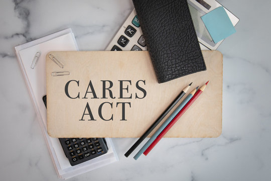 Cares Act sign on wooden sign with office materials laying around government financial aid programs small business relief
