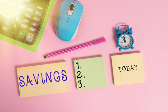 Text sign showing Savings. Business photo text the money that a demonstrating keeps in an account in a bank or like Notepads mouse alarm clock calculator sheet marker colored background
