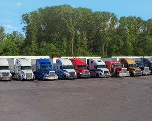 Modern trucks of various colors and models  transportation of different kinds of commercial goods stand in row on truck stop parking lot for truck driver rest according to log book.