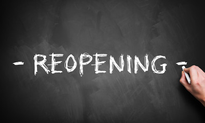 hand writing REOPENING on blackboard