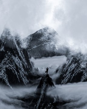 Silhouette Man With Arms Raised Standing On Mountain Peak During Winter