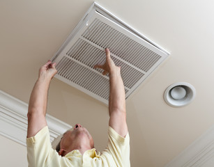 Low Angle View Of Senior Man Adjusting Air Duct