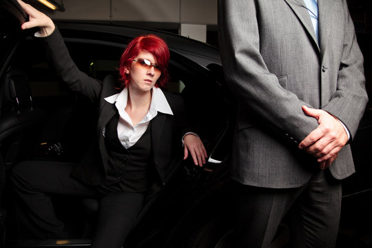 Businesswoman Disembarking From Car By Bodyguard