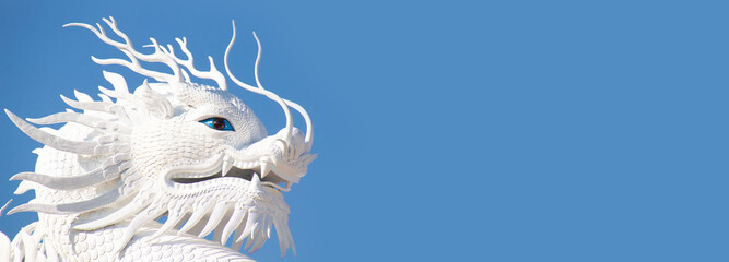 White dragon statue on blue sky background.Dragon is fairy tale monster in many culture around the world.
