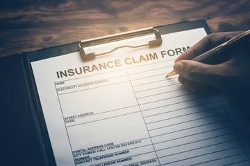Close-up Of Cropped Hand Filling Insurance Claim Form On Desk