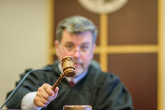 Close-up Of Judge Banging Gavel In Courtroom