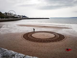 Man Drawing On Beach Against Sky