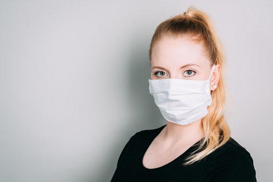 Junge Frau trägt Schutzmaske während Maskenpflicht vor neutralen Hintergrund