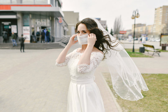 Bride in medical mask on street of city during coronavirus epidemic. Wedding day COVID-19 protection