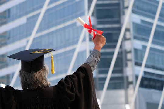Rear View Of Man Wearing Graduation Gown Against Building