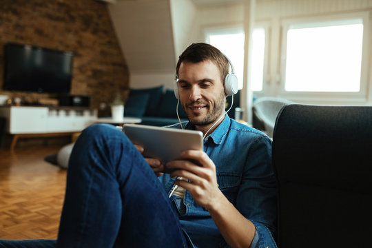 Smiling man with headphones using digital tablet at home.
