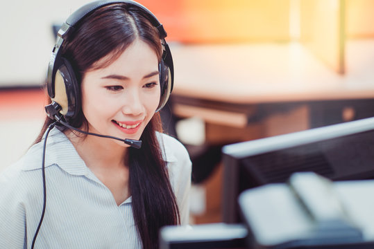 Smiling Customer Service Representative With Hands-free Device Working In Office