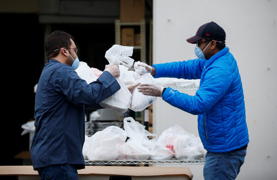 Volunteers hand out free iftar meals to community members outside the Muslim Association of Puget Sound on the first day of Ramadan during the coronavirus disease (COVID-19) outbreak in Redmond