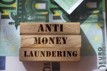Anti Money laundering concept, words on wooden blocks on 100 euro banknotes