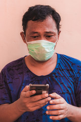 Asian man wearing face mask shows expression. The concept of people having to wear masks in public during  the COVID-19 pandemic or coronavirus disease crisis.