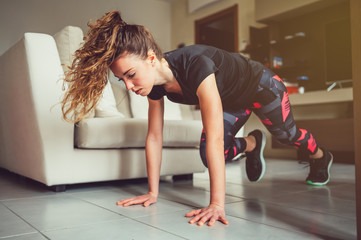 Giovane bella ragazza realizza esercizi fisici a casa. Esercizi funzionali a corpo libero nel salotto di casa