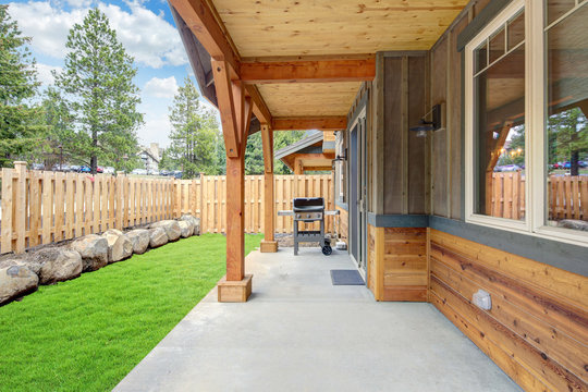 Small new back yard with wooden house and fence, fresh grass and BBQ on the concrete porch.