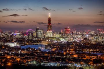 Fotomurales - Die Skyline von London, Großbritannien, am Abend mit den beleuchteten Wolkenkratzern und zahlreichen Touristenattraktionen
