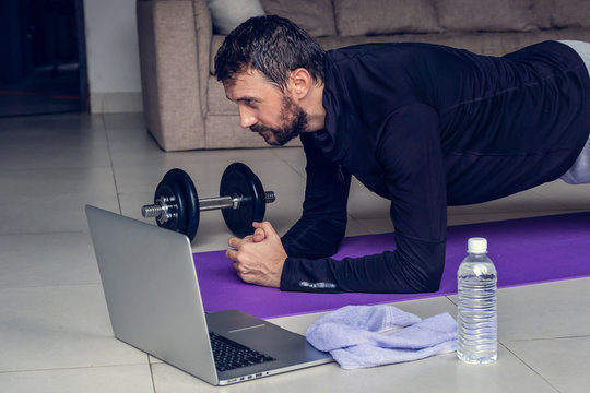 Young man exercising and plank working out online with laptop or phone at home during covid-19 pandemic quarantine. Sports and healthy lifestyle concept