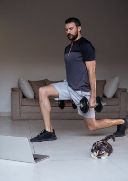 Young man exercising and working out with weights online with laptop or phone at home during covid-19 pandemic quarantine. Sports and healthy lifestyle concept