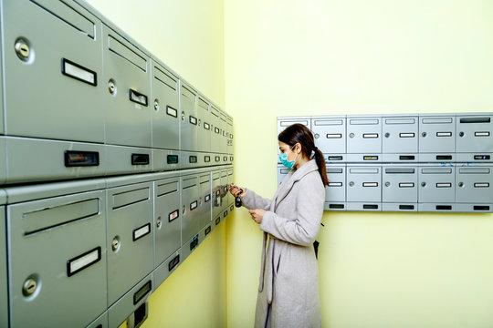 Ragazza con cappotto e mascherina di protezione verifica se c'è posta nella sua cassetta delle lettere
