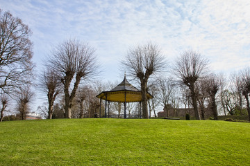 Empty Colchester Castle Park in England during lockdown in April 2020 due to coronavirus quarantine with bandstand and castle in the background.