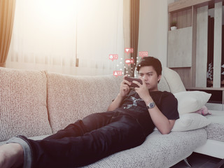 Digital Composite Image Of Man Using Phone With Icons While Relaxing On Sofa At Home