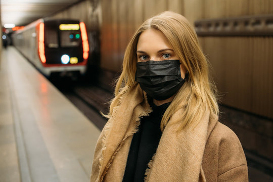 Girl in black medical mask standing next to subway car.