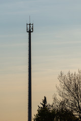 Telecommunication tower with cellular network antenna against blue sky as background