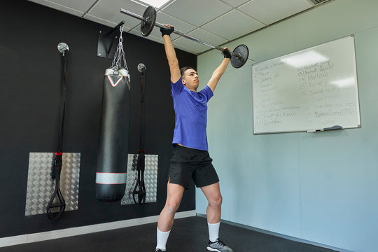 Fit young man in sportswear lifting weights in her workout in gym