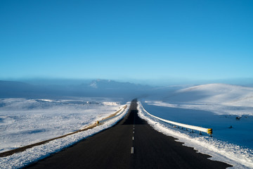 Empty Road Leading Towards Snowcapped Mountains Against Clear Blue Sky