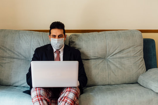 Executive businessman with a mask on his face working from home with his laptop. Dressed in a suit and tie and pajama pants. Sitting on the couch. Concept work from home. Coronavirus pandemic.