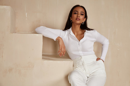 Beautiful sexy brunette woman tanned skin face cosmetic makeup wear white suit pants for date walk office fashion clothes style collection interior room  sand color safari summer casual.