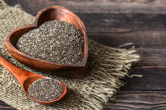 chia seeds in a wooden bowl and spoon on a wooden table and burlap close-up. background with chia seeds. healthy food with chia seeds.