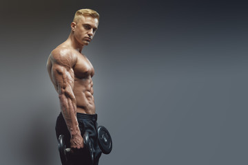 Young strong fit muscular sweaty man with big muscles strength cross workout training with dumbbells weights in the gym. Copy free space on right