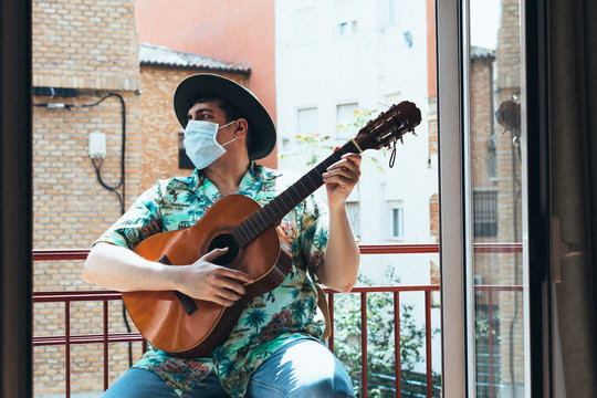 Bohemian musician with mask on his face and hat playing the Spanish guitar from his balcony. Dressed in a Hawaiian shirt and jeans Concept music from home during confinement. Coronavirus pandemic.