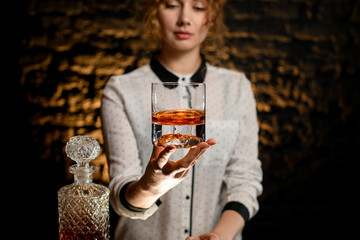 Young beautiful bartender woman hold old-fashioned glass with alcoholic drink