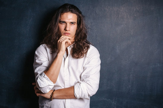 Handsome happy man in white shirt. Smiling guy with long hair on isolated background in studio. Sexy confident boy