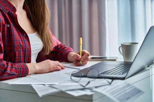Woman blogger working remotely on laptop and writing down important data information in notebook dairy. Female during distance education and online courses learning at home