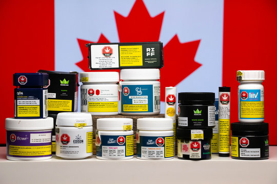 Retail cannabis in original packaging by various licensed providers of legal marijuana in Canada. Canadian flag as a background.