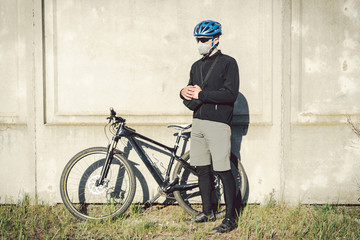 A man cyclist in a protective face mask stands next to a bicycle on a background of gray concrete wall. Unrecognizable Courier in respirator. Delivery service during a pandemic