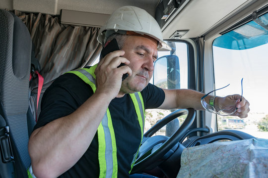 Truck driver with helmet and safety glasses talking on the phone and looking at a map