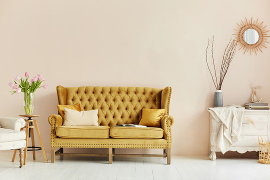 Cozy living room interior of retro armchair, vintage wooden chest dwarf and vintage couch on the background of the beige wall and painted wooden floor