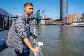 Wall Mural - Young man standing on a ferry crossing Hudson river to Manhattan.